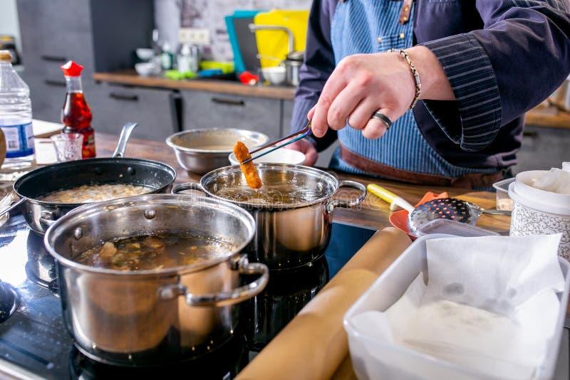 Kocken drar ut stekte fiskstycken i smet Mästarklass i köket Processen av matlagning Begrepp med mänskliga fotspår tutorial Närbi royaltyfri bild