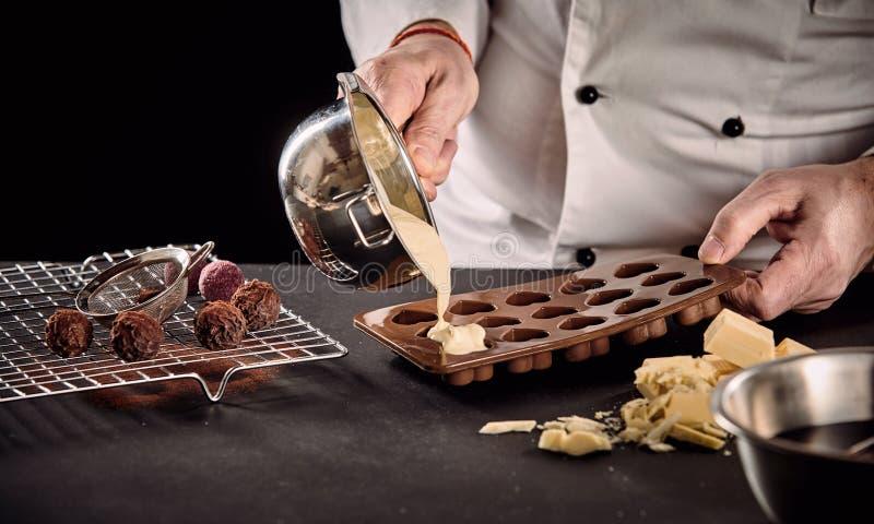 Kocken eller mer chocolatier hälla smältte vit choklad royaltyfri bild