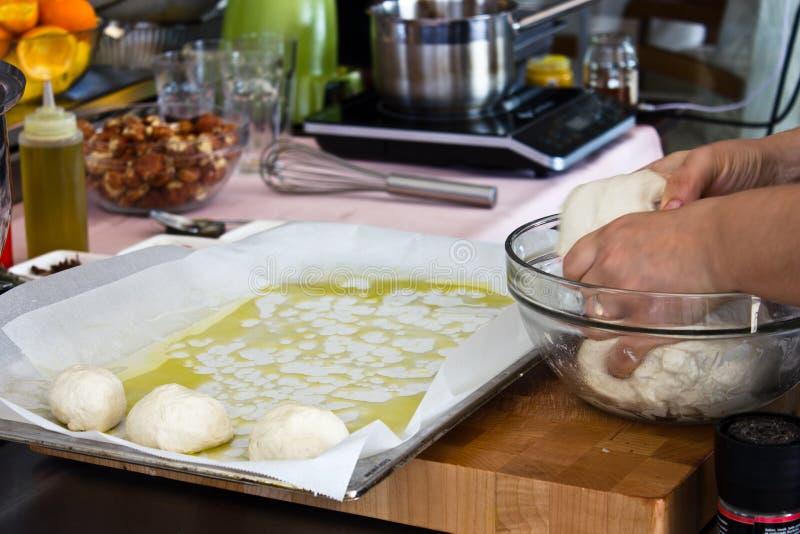 Kocken förbereder bullar från jästdeg och spridningar på en bakning royaltyfri bild