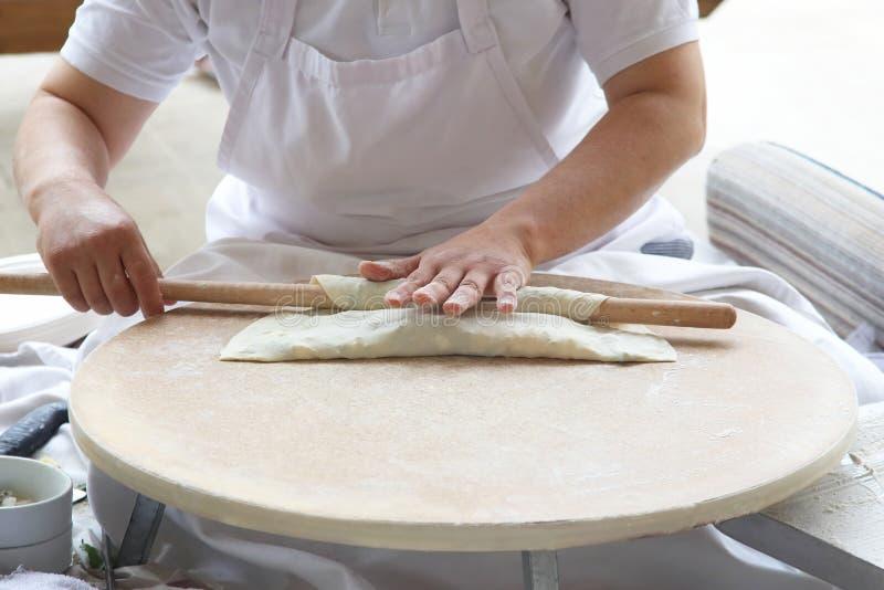 Kocken förbereder degen med fyllning arkivbild