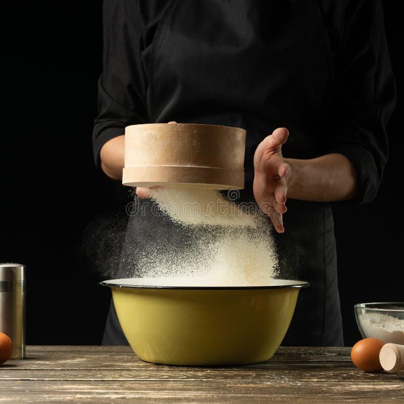 Kocken förbereder degen på en mörk bakgrund Frost i luften Förberedelse av läcker mat, allt mjöl arkivfoton