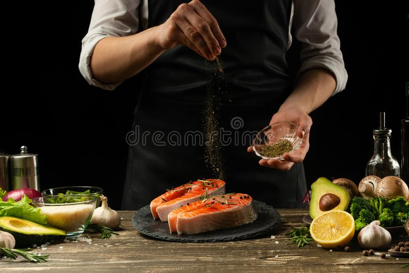 Kocken förbereder den nya laxfisken, den nya laxen, stänk med kryddor och Provencal örter med ingredienser Frost i luften fotografering för bildbyråer