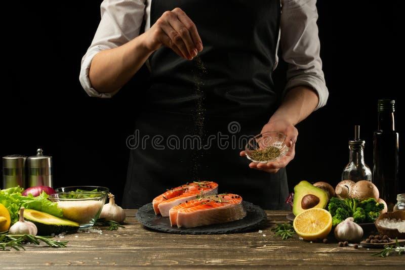 Kocken förbereder den nya laxfisken, den nya laxen, stänk med kryddor och Provencal örter med ingredienser Frost i luften royaltyfria foton