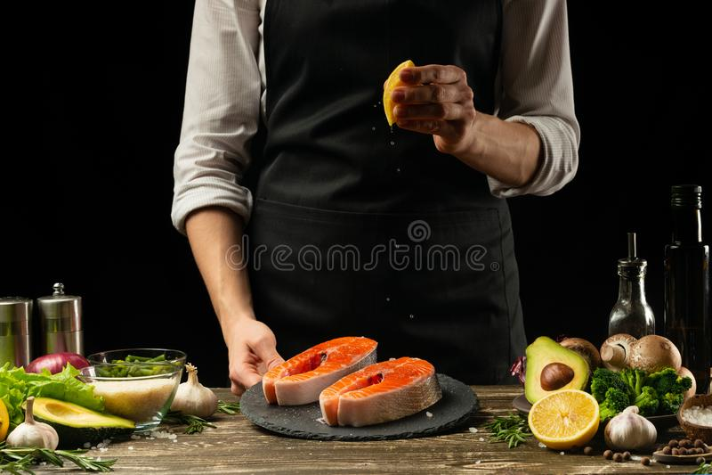 Kocken förbereder laxen för den nya fisken, forellen, citron som bevattnar med grönsaker för bildfoto för kustlinje grön horisont arkivfoto