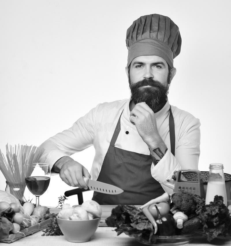 Kocken förbereder mål Kock med den fundersamma framsidan i den burgundy likformign arkivfoto