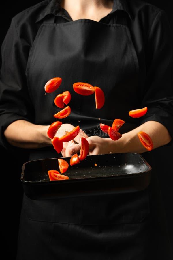 Kocken förbereder tomatsås, steker tomater, körsbärsröda tomater i en stekpanna, frysningar, pasta, pizza processmoment i arkivfoton