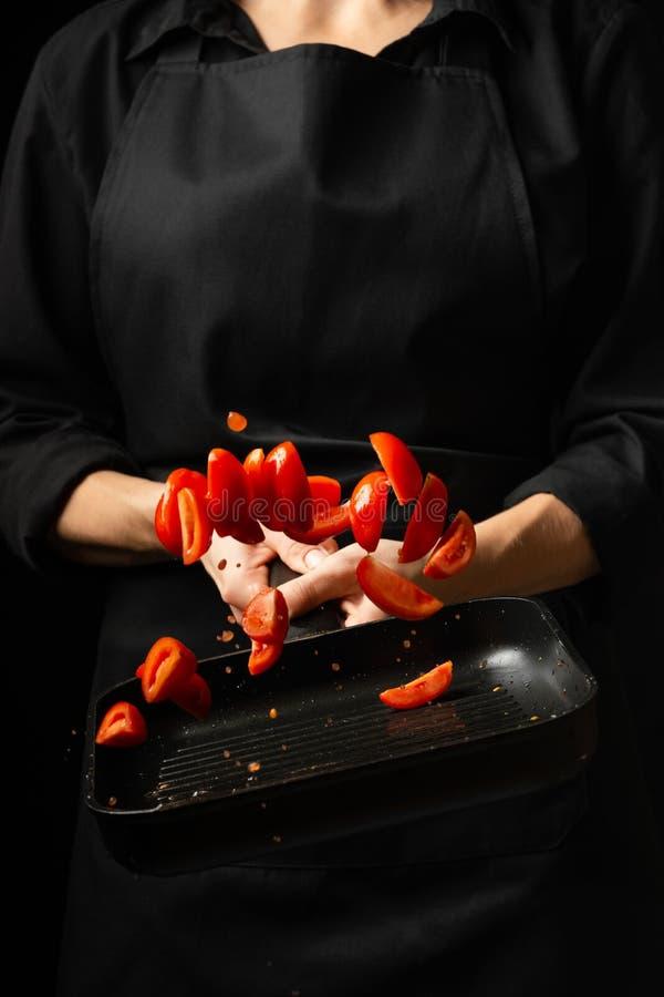 Kocken förbereder tomatsås, steker tomater, körsbärsröda tomater i en stekpanna, frysningar, pasta, pizza processmoment i royaltyfri bild