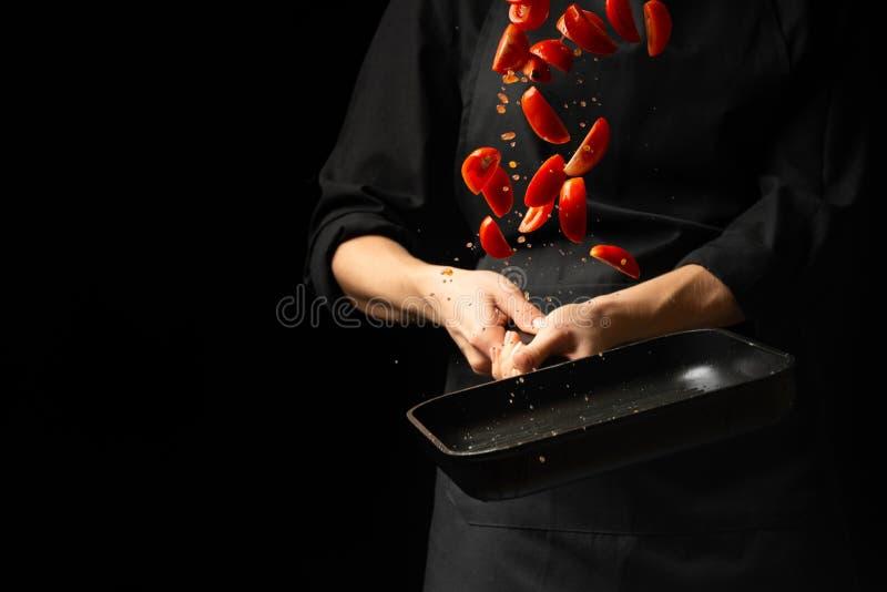 Kocken förbereder tomatsås, steker tomaterna, körsbärsröda tomater i en stekpanna, frysning, för pasta, pizza moment bearbetar på royaltyfri foto