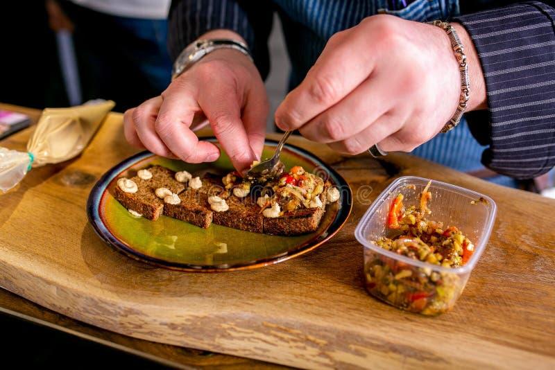 Kocken fördelar bakade grönsaker på stekt hantverkbröd Mästarklass i köket Processen av matlagning Begrepp med mänskliga fotspår  royaltyfri fotografi