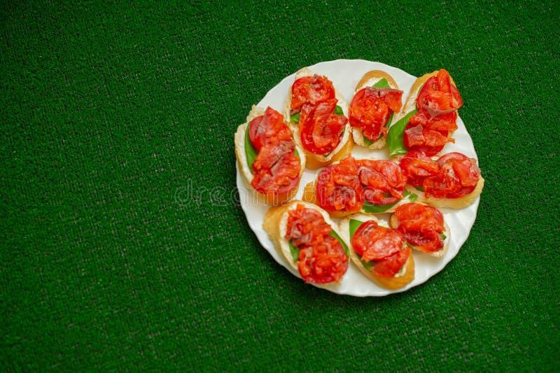 Kocken fördelar keson på brödet med tomaten arkivfoto