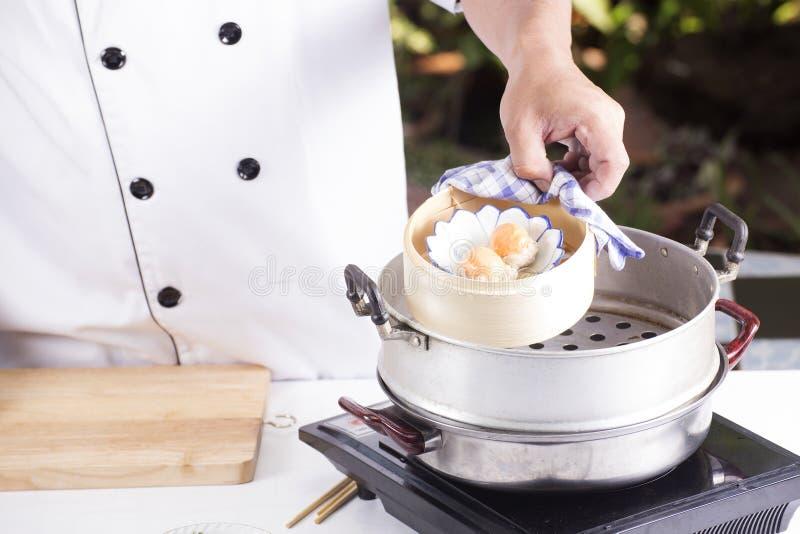 Kocken framlade ångafärsgriskött och det saly röda ägget Dim Sum arkivbild