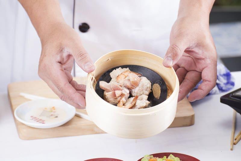 Kocken framlade ångafärsgriskött och korvkines Dim Sum royaltyfri fotografi