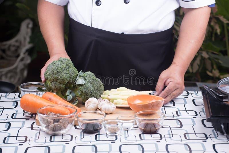 Kocken framlade broccoli för ingrediensuppståndelsesmåfisk med räka arkivfoto