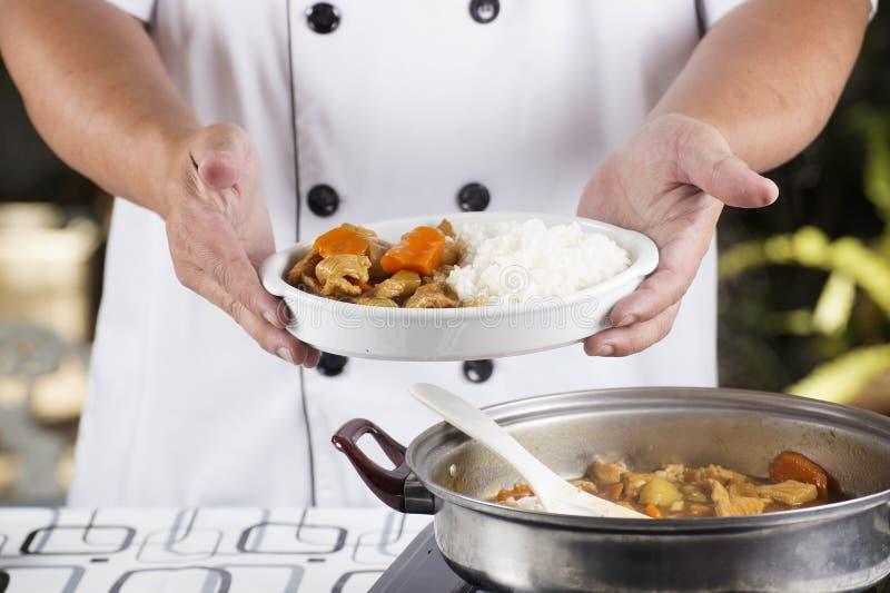 Kocken framlade japansk grisköttcurry med ångaris royaltyfri bild