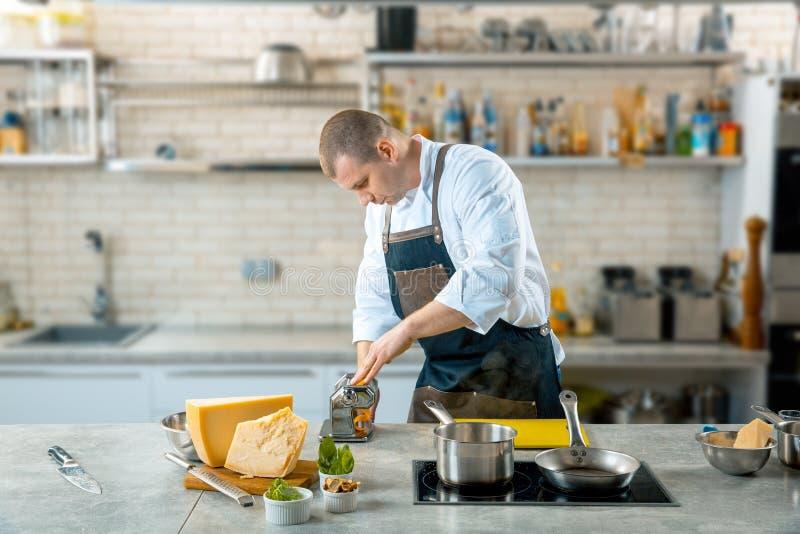 Kocken gör tunn deg med den speciala maskinen, tonad bild royaltyfria bilder