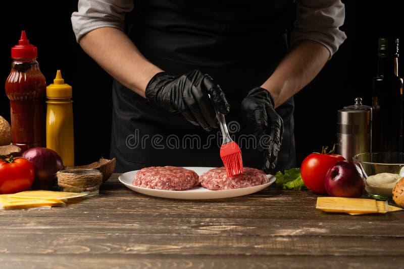 Kocken gnider nötkötthamburgare med smör, mot bakgrunden med ingredienser, en restaurangaffär, snabbmat, smaklig mat, royaltyfri bild