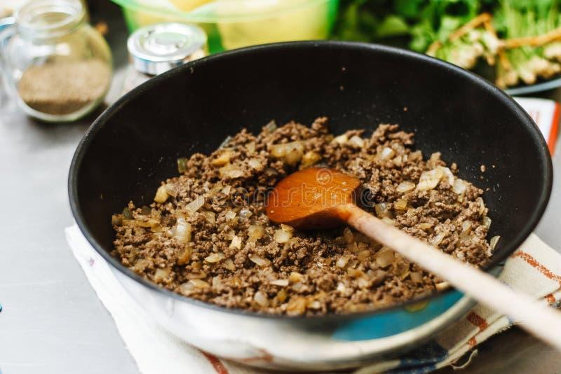 Kocken grillar finhackar i en djup panna Klart stoppa med lökar i en bunke på bakgrunden av kryddor och gräsplaner arkivfoto