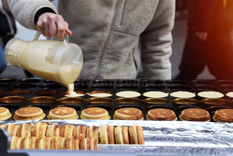 Kocken häller degen på ugnen med ett hål för framställning av pannkakor arkivbild