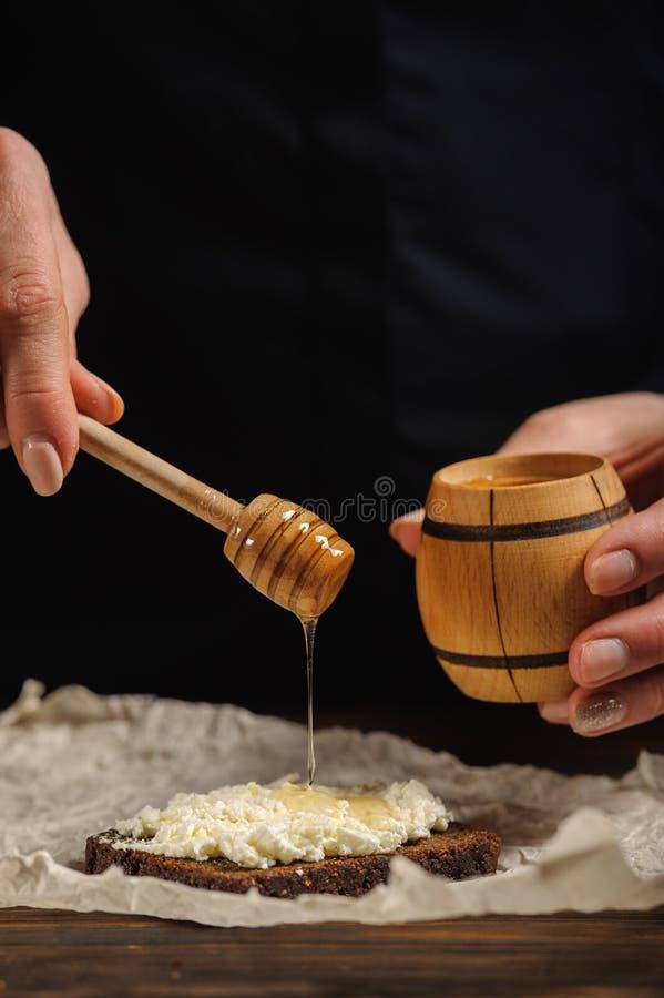Kocken häller honung på bröd royaltyfria bilder