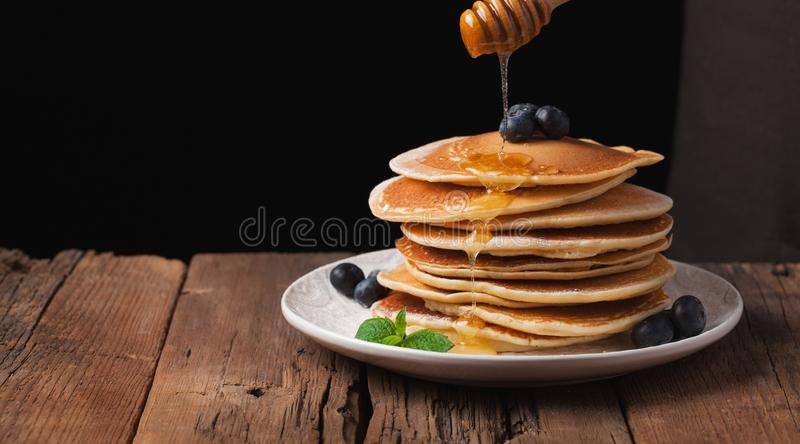 Kocken häller honungpannkakabunten med blåbär och mintkaramellen på svart bakgrund kopiera avstånd för din text arkivfoton