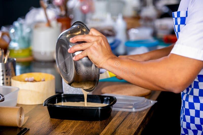 Kocken häller smeten ut ur bunken in i en stekhet maträtt Mästarklass i köket Processen av matlagning Begrepp med mänskliga fotsp arkivfoton