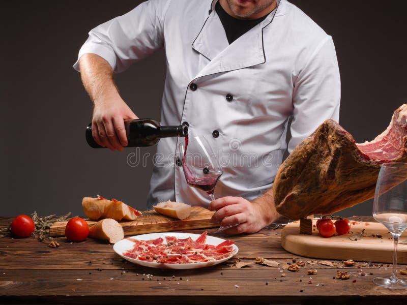 Kocken häller vinet in i ett exponeringsglas En flaska av vin, kryddor, jamon, tomater, en trätabell Closeupbild royaltyfria bilder