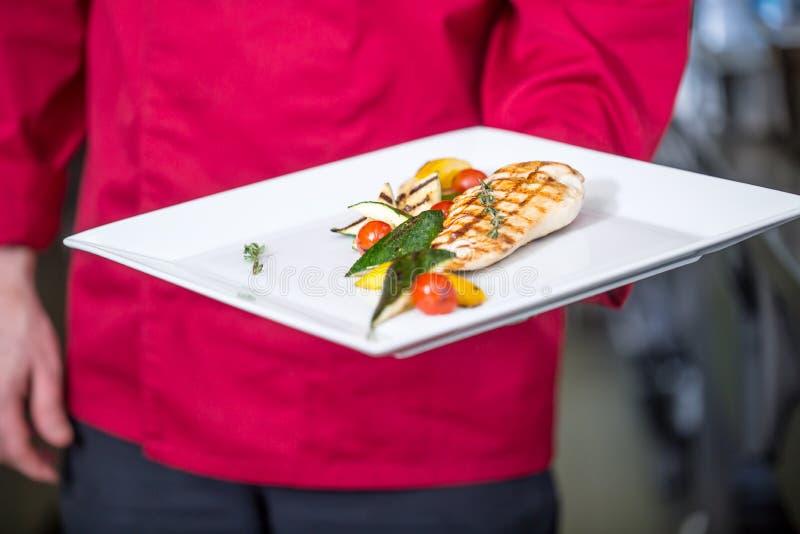 Kocken i hotell- eller restaurangköket förbereder mål Kock med grillade grillade grönsaker för fegt bröst på den vita plattan royaltyfri foto