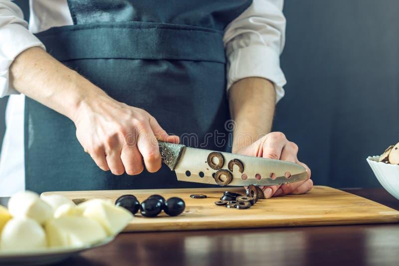 Kocken i svart förkläde klipper svarta oliv med en kniv Begrepp av eco-vänskapsmatch produkter för att laga mat royaltyfri fotografi