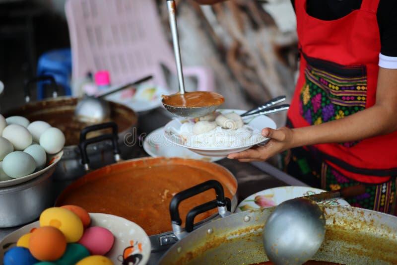 Kocken kammar hem grisköttcurry och gröna grönsaker i en tappningrestaurang, gatamat royaltyfria foton