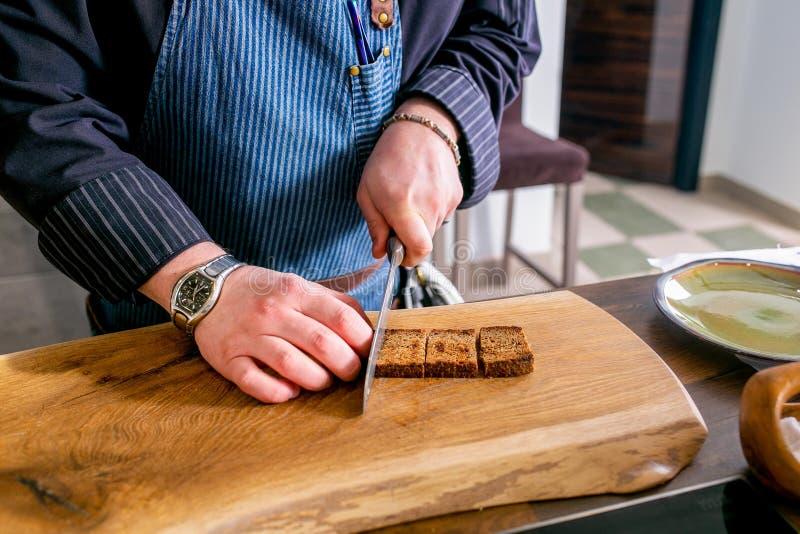 Kocken klipper grillat bröd Mästarklass i köket Processen av matlagning Begrepp med mänskliga fotspår tutorial Närbild royaltyfri fotografi
