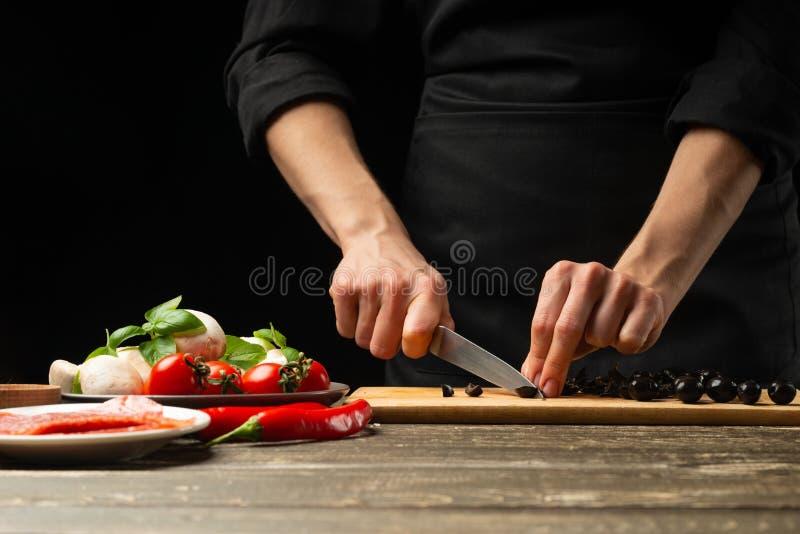 Kocken klipper oliven För förberedelsen av pizza sallad Ett läckert målbegrepp På en svart bakgrund för design eller arkivbild
