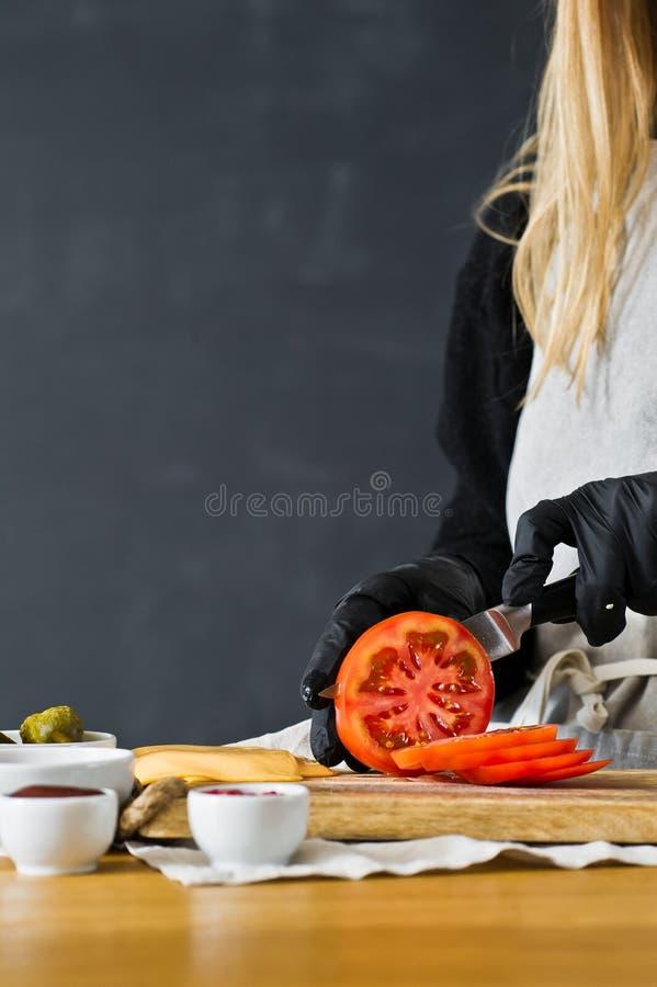 Kocken klipper r?da tomater Begreppet av att laga mat en svart hamburgare K?k sidosikt, utrymme f?r text arkivfoton