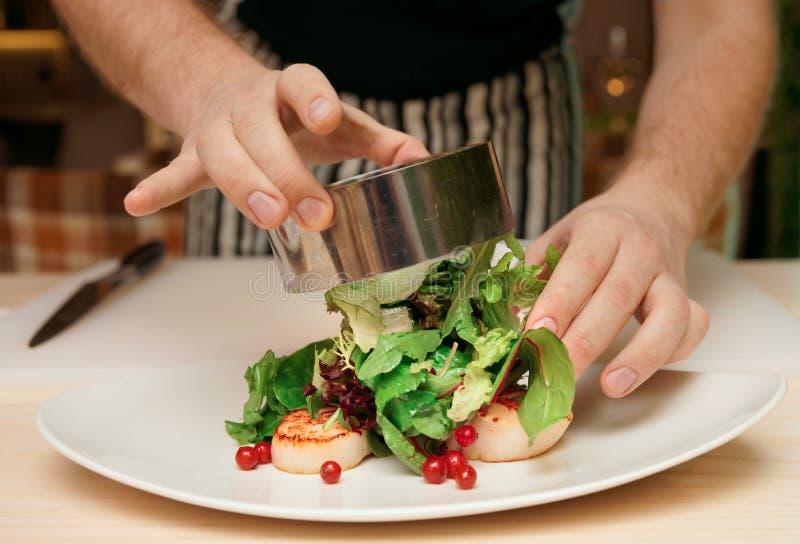 Kocken lagar mat aptitretaren med kammusslor arkivbild