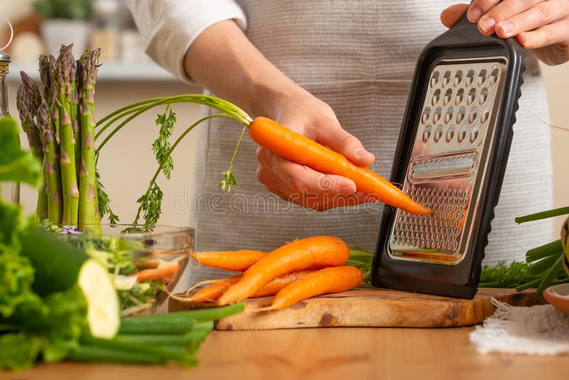 Kocken lagar mat nya morötter för sallad Begreppet av förlorande sund och hälsosam mat, detoxen, strikt vegetarian som äter, bant arkivbilder