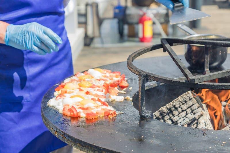 Kocken lagar mat stekte ägg med tomater på festivalen Gatamat som förbereds på galler arkivbilder