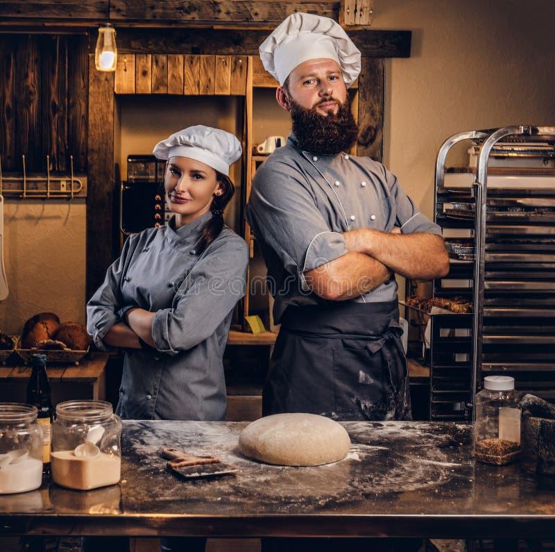 Kocken med hans assistent i kocklikformign som poserar med korsade armar nära, bordlägger med klar deg i bagerit arkivfoto