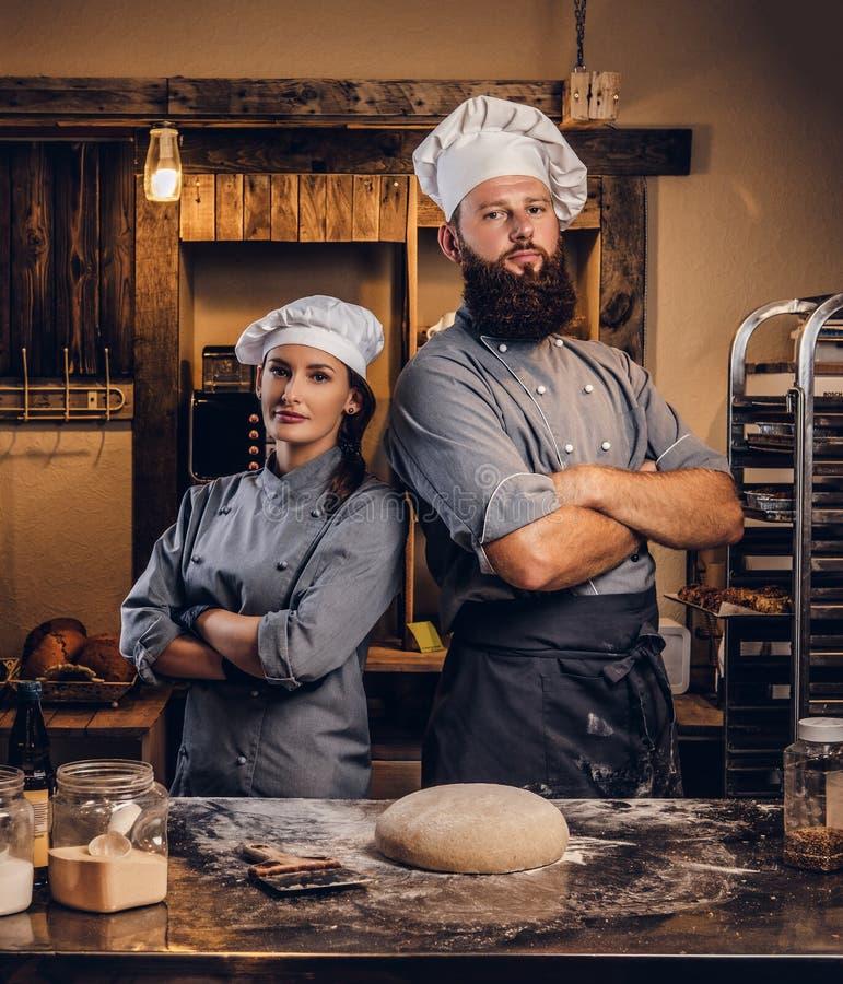 Kocken med hans assistent i kocklikformign som poserar med korsade armar nära, bordlägger med klar deg i bagerit royaltyfri foto