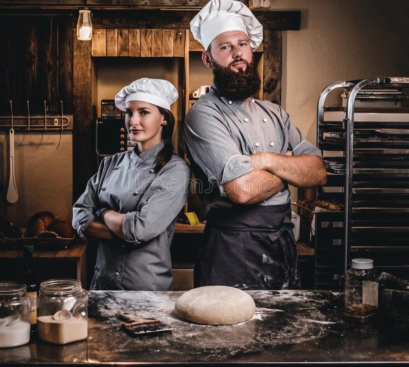 Kocken med hans assistent i kocklikformign som poserar med korsade armar nära, bordlägger med klar deg i bagerit royaltyfri bild