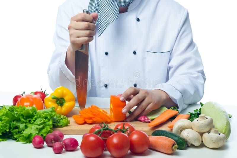 Kocken räcker villigt att arbeta i bakgrundsgrönsakerna arkivbilder