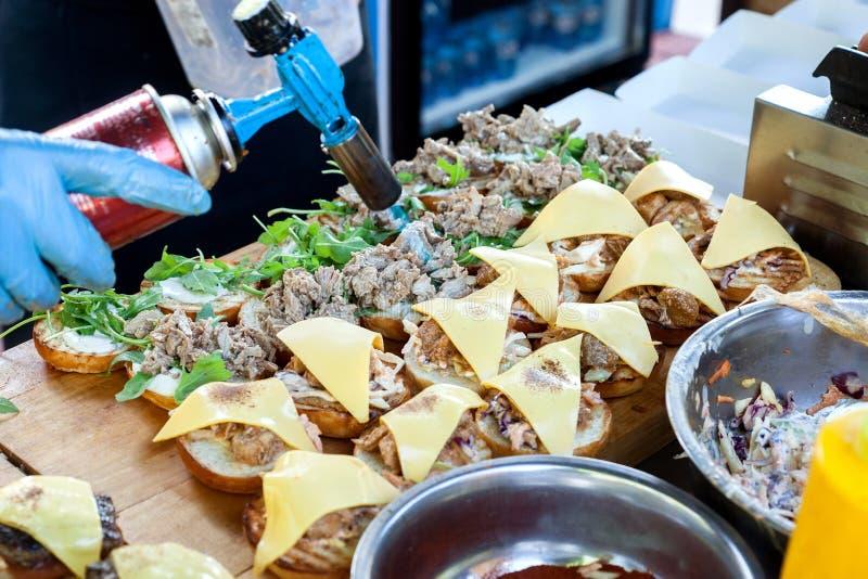 Kocken smälter osten med facklan, medan laga mat hamburgare Gatasnabbmat royaltyfri foto
