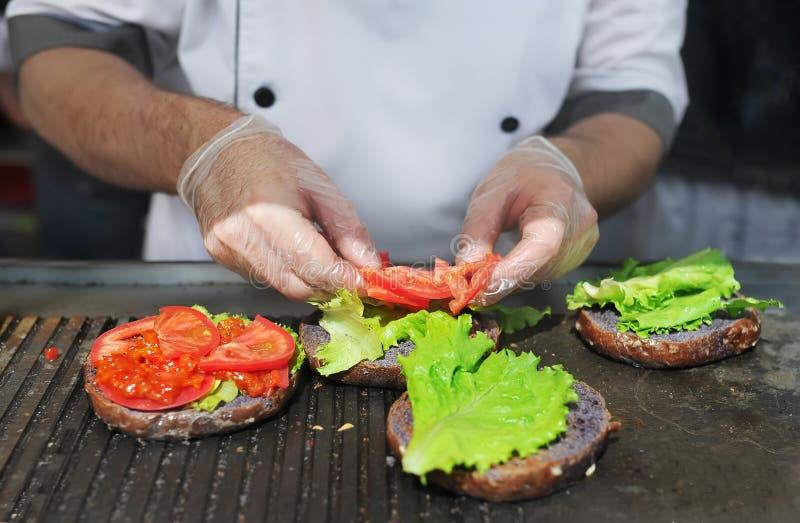 Kocken som förbereder hamburgaren som tillfogar tomaten Ingredienser för förberedelse av hamburgare arkivbilder