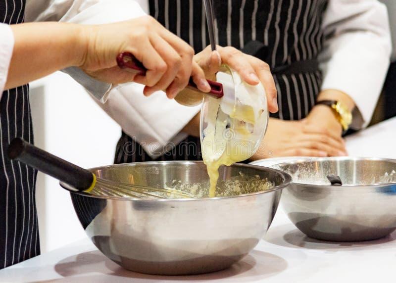 Kocken som gör deg på kök, blandande smör, mjölkar den bakelsebagerit, kocken och kakan arkivbilder