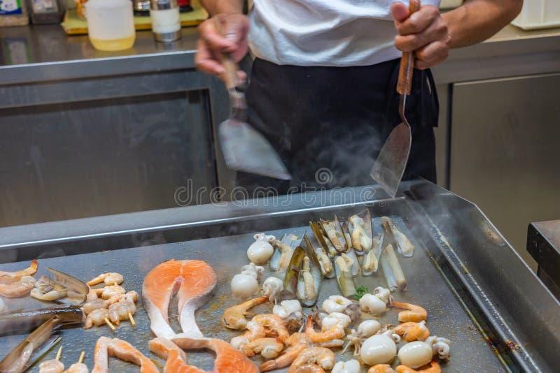 Kocken som grillar sortimentet av skaldjur i restaurangs kök royaltyfri bild