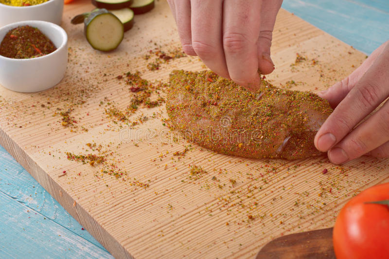 Kocken strilar det fega bröstet för kryddiga kryddor fotografering för bildbyråer