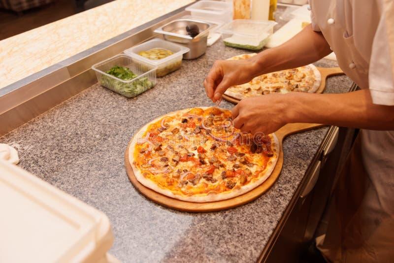 Kocken tjänar som pizza royaltyfri bild