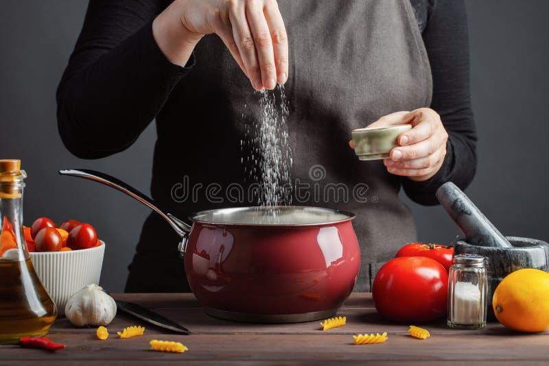 Kockförberedelserna spagetti och pasta, saltar vatten, mot en mörk bakgrund, begreppet av att laga mat Kvinna som saltar vatten arkivfoton