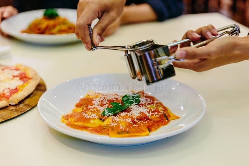 Kockhand som skivar parmesanost på raviolit med tomatsås och basilika i den vita plattan på den vita bordduken arkivfoton
