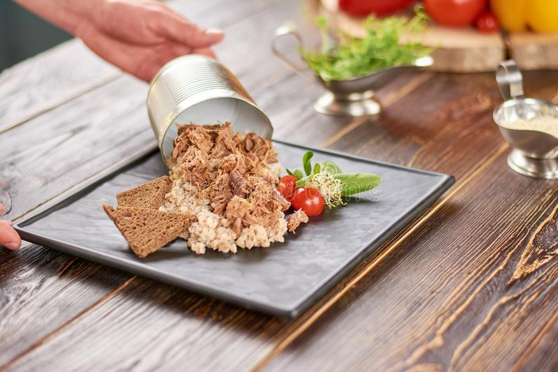 Kockhand som ut häller kött från canen royaltyfri foto