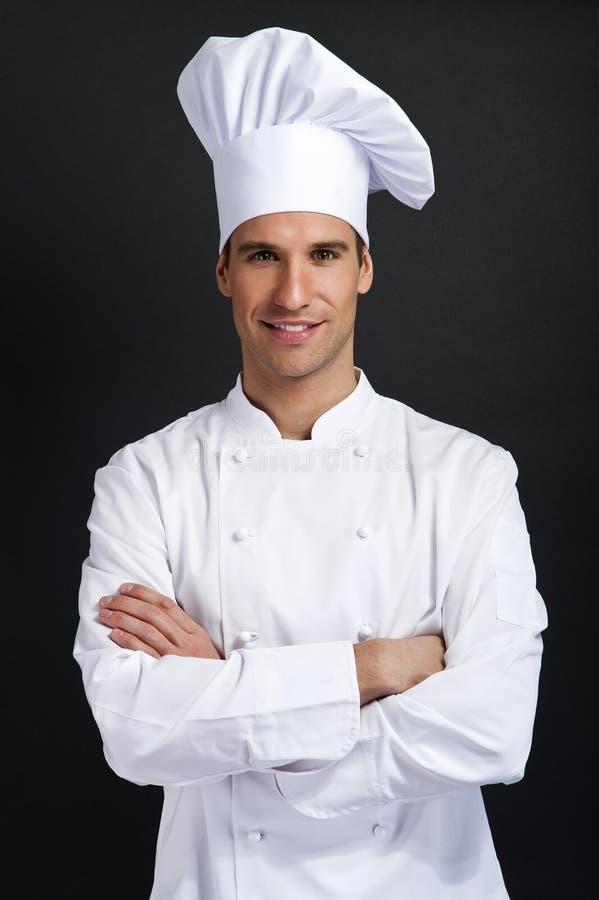 Kockkock mot mörk bakgrund som ler med hattholdinfskeden royaltyfri bild