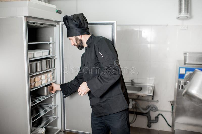 Kockkock som får mat från kylskåpet arkivbild